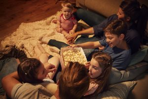 Family sitting together on floor eating popcorn while watching movies.